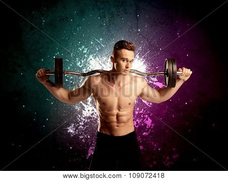A sexy male fitness trainer showing his muscles and looking seductive with a weight in his hands in front of bright paint splash purple wall concept
