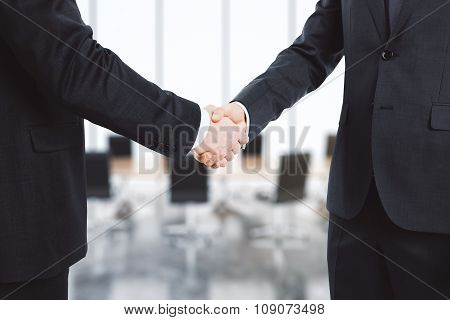 Businessmen Shake Their Hands In Conference Room