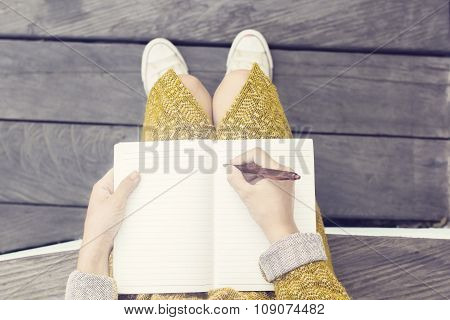 Girl With Blank Diary And Pen Sitting On Wooden Bench