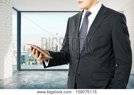 Businessman With Digital Tablet In Loft Style Room With Megapolis City View