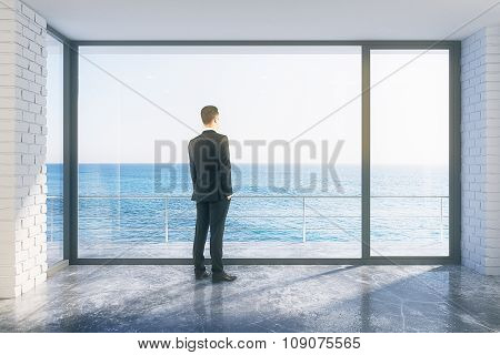 Businessman In Empty Loft Room With Big Window In Floor And Ocean View