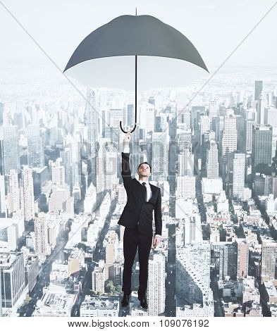 Flying Businessman With Umbrella At Megapolis City Background