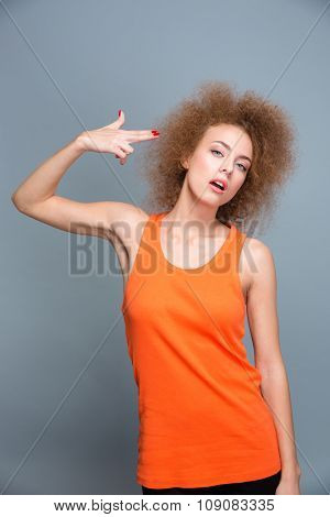 Young emotional curly woman in orange top with a finger to her temple like a gun posing on gray background