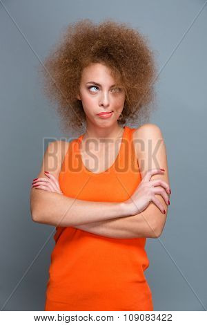 Bored annoyed curly pretty young woman looking up and posing with crossed arms on gray background