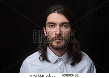 Portrait of a man with beard and long hair looking at camera isolated on a black background