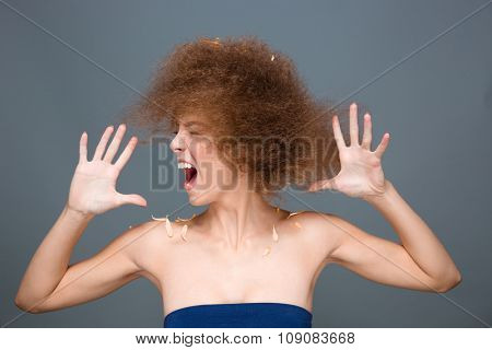 Hysterical excited curly emotional energetic young woman screaming and shaking her head