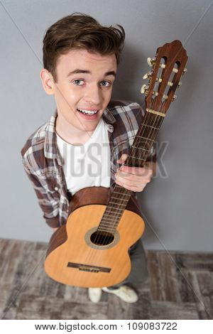 Top view portrait of a young man standing with guitar and looking at camera