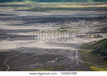 Aerial view of sea of sand inside Bromo Tengger Caldera. Pura Luhur Poten temple and jeep parking.