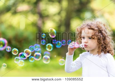 A Little Girl Blowing Soap Bubbles, Closeup Portrait Beautiful Curly Baby