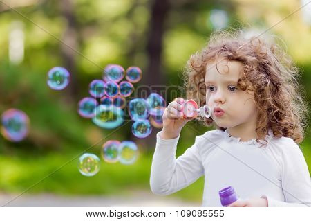 A Little Girl Blowing Soap Bubbles, Closeup Portrait Beautiful Curly Bab