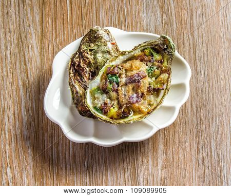 Salad in oyster at white plate on a wooden background.