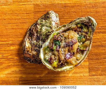 Salad in oyster on a wooden background.
