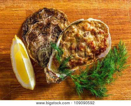 Baked oyster shell with cheese, served greens and lemon
