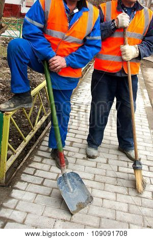 Two workers with a shovel and broom.