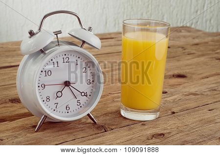 Glass Of Orange Juice With An Alarm Clock