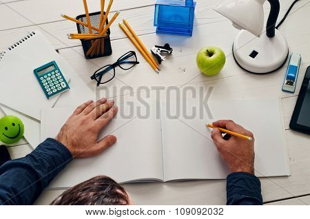 Designer Sitting At A White Wooden Desk And Working