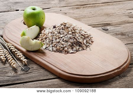 Handful Of Oatmeal On A Wooden Cutting Board With Apples