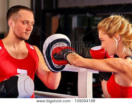 Female boxer  throwing  right cross at mitts with her trainer in ring. Kinds of fitness.