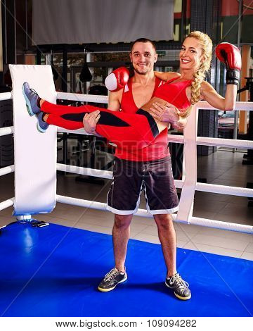Female boxer with your male coach after workout in gym. Man carry girl in his arms. They standing on ring.