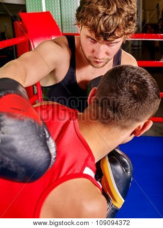 Two aggresive men boxer wearing  and  gloves boxing .