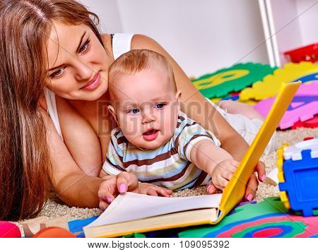 Kid baby boy with mother  lying on floor and plying with puzzle toy at home.