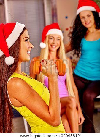 Girls in Santa hat holding dumbbells in sport gym. Sport Christmas concept