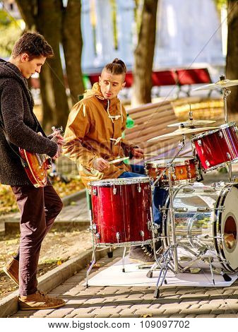 Music street male performers playing percussions on sun day autumn outdoor.