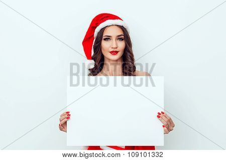 Beautiful girl in the hat of Santa Claus. Hold a sheet of paper. Red manicure. Red lips.