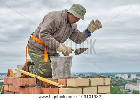 Bricklayer works on 15th floor of building