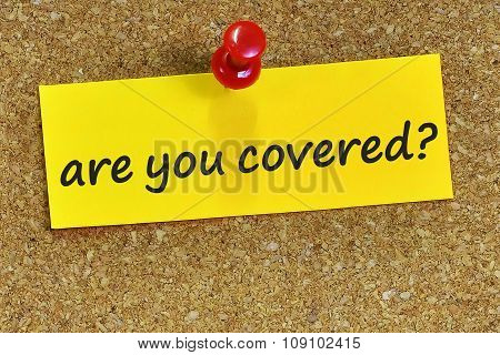 Are You Covered? Word On Yellow Notepaper With Cork Background