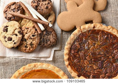 Assorted holiday desserts including:  gingerbread, pumpkin pie, pecan pie, chocolate chip and oatmeal raisin cookies,