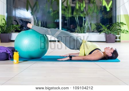 Side view of woman doing half bridge pose in fitness studio practices piltes or yoga warming up exer