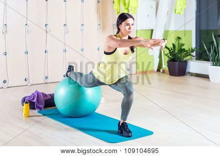 Woman doing a one leg squat pilates exercises with fit ball in gym or yoga class.