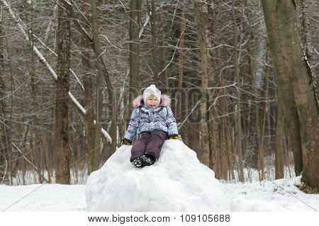Smiling little girl wearing warm clothes posing on snowy hill in winter forest