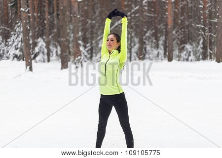 Fit woman stretching, warming up morning winter training.
