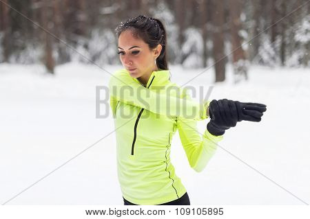 Fit woman warm up stretching her arm and shoulder winter.