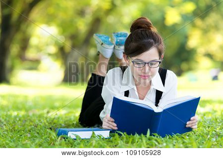 Smiling Casual Student Lying On Grass Reading Book
