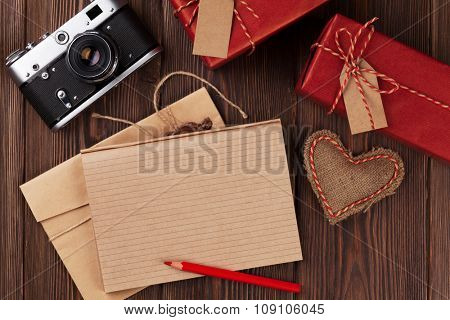 Valentines day toy heart, retro camera, gift boxes and notepad for your text. Top view on wooden table