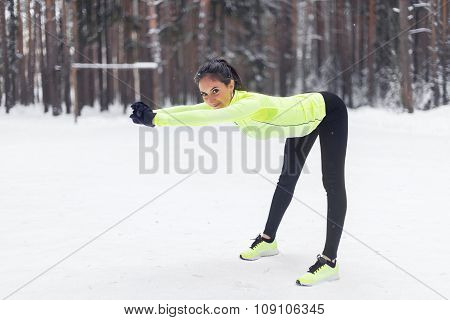 Cheerful young woman exercising  doing warming up Winter forest park.