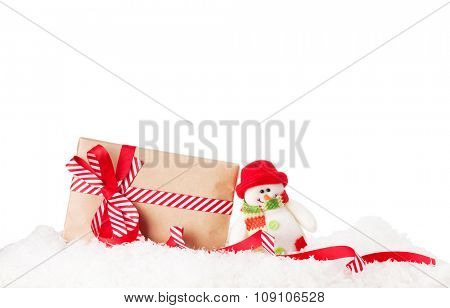 Christmas gift box and snowman toy in snow. Isolated on white background