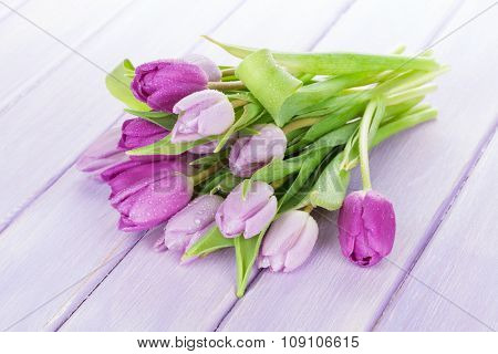 Purple tulips bouquet over wooden table