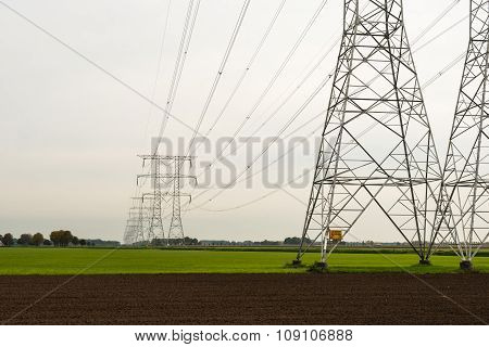 Row Of Power Pylons In An Agricultural Area