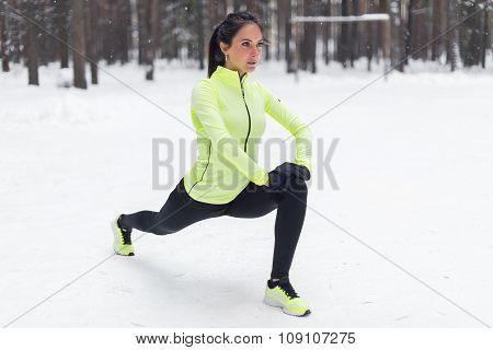 Fit woman doing stretching exercises before running outdoors Winter street training.