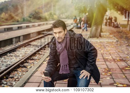 Handsome Traveller With Cellphone At Train Station