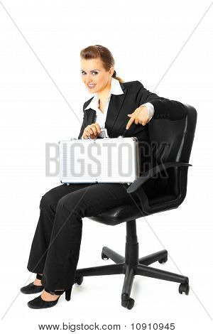 Smiling modern business woman sitting on chair and pointing finger on suitcase in her hand
