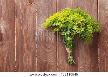 Fresh garden dill on wooden table. Top view with copy space