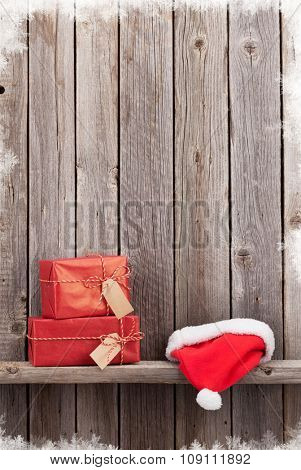Christmas gift boxes and santa hat in front of wooden wall. View with copy space