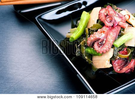 Japanese salad with octopus and ginger. Healthy food. Seafood closeup over black background