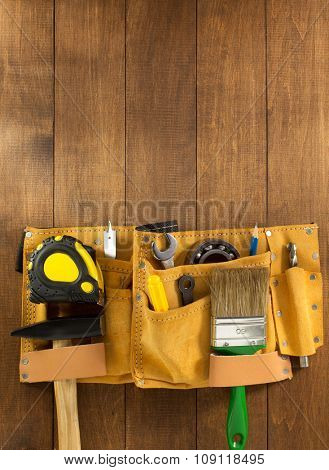 tools and instruments in belt on wooden background