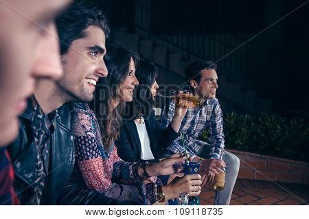 Woman holding cocktail whit her friends in a party